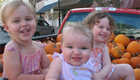 three girls sitting with pumpkins